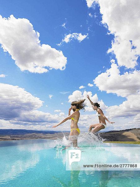 Frauen springen im Schwimmbad