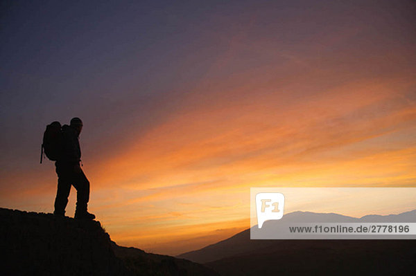 Wanderer mit Blick auf den Sonnenaufgang.