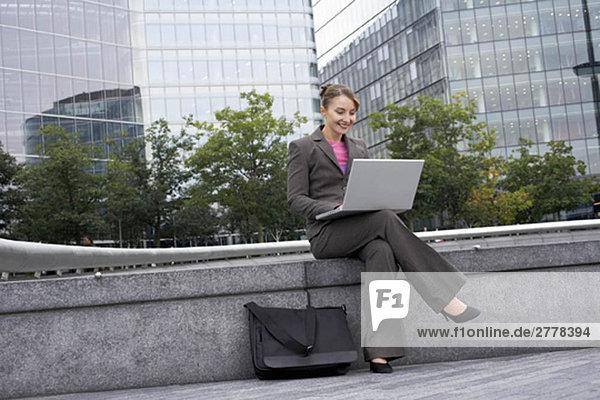 Geschäftsfrau mit Laptop im Freien