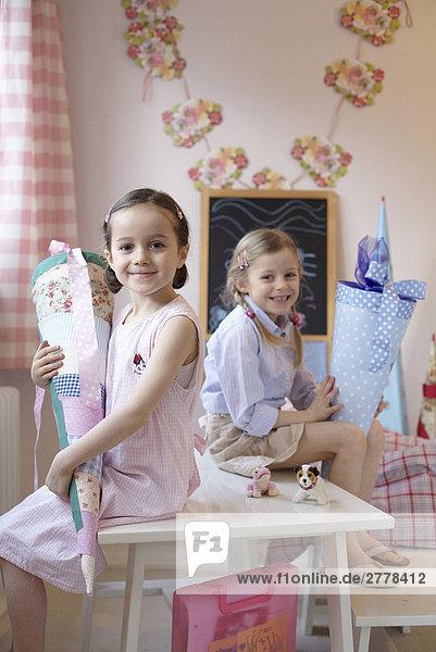 Portrait von zwei Mädchen Pappe Zapfen hält und lächelnd auf Tabelle
