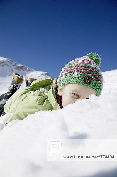 Porträt des Mädchens auf Schnee liegen