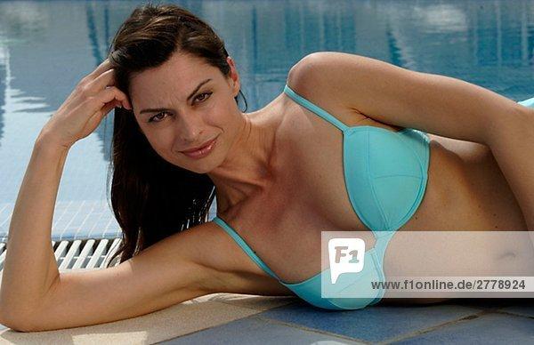 Frau im türkisfarbenen Bikini liegt am Swimmingpool - Kopf aufgestützt