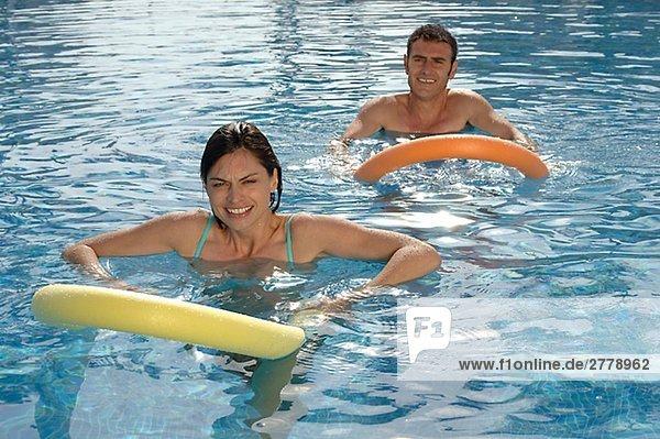 Paar im Swimming Pool mit Ringen