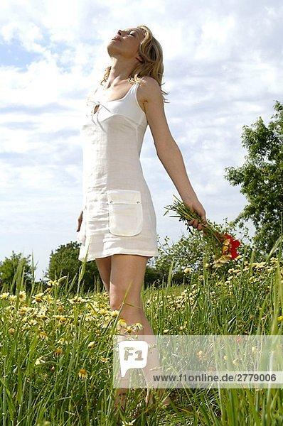 Frau mit Blumenstrauß genießt die Sonne inmitten einer Sommerwiese