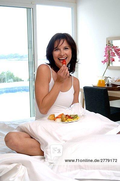 Frau im Bett mit Obstteller