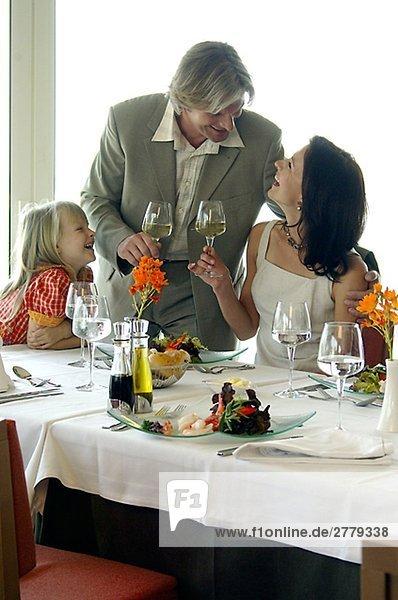 Familie am gedeckten Tisch mit Weingläsern