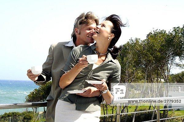 Paar am Meer trinkt Kaffee