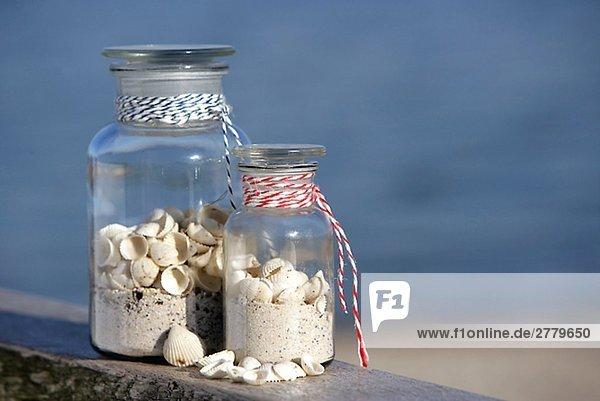 Zwei Apothekerflaschen mit Sand und Muscheln gefüllt