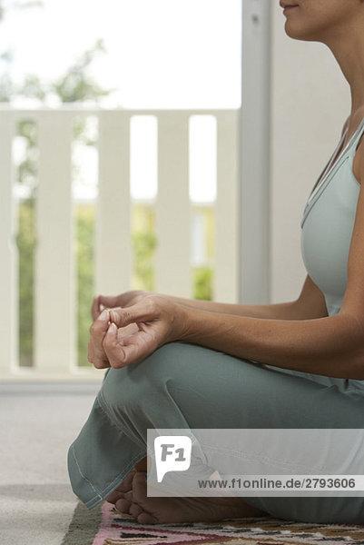 Mixed Race Frau sitzt in Lotus Pose auf Veranda