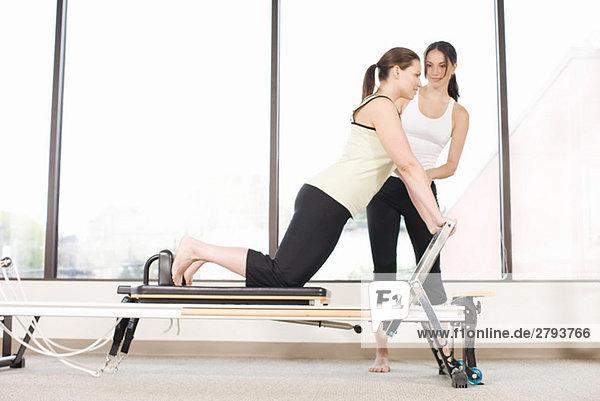 Personal-Trainer Leitlinien Frau auf Pilates Ausrüstung