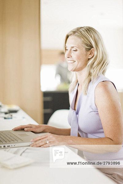 Frau mit Laptop im home-office Heimarbeitsplatz
