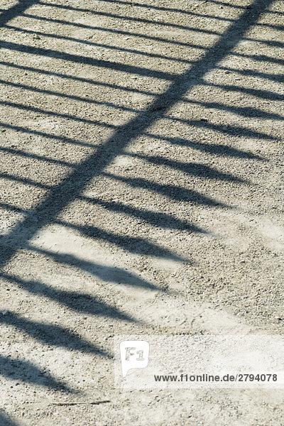 Schatten des schmiedeeisernen Zaun auf Kies