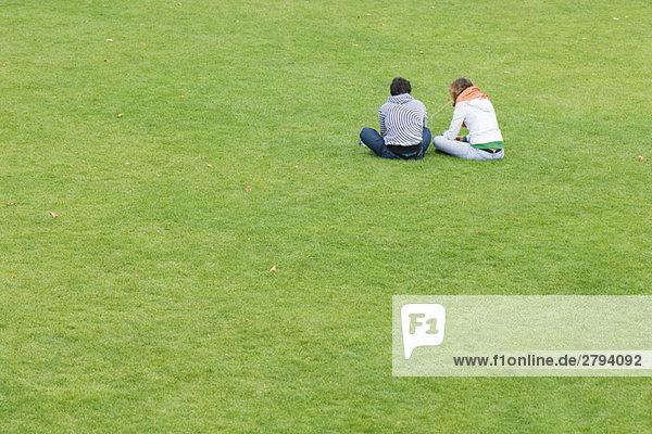 Junges paar sitzen nebeneinander auf Rasen  Rückansicht