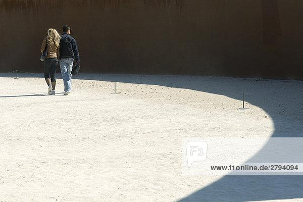 Couple walking on sunlit gravel  rear view