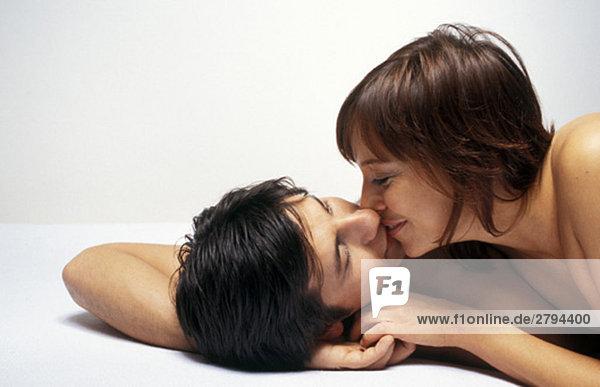 Ein Paar liegt zusammen und küsst sich.