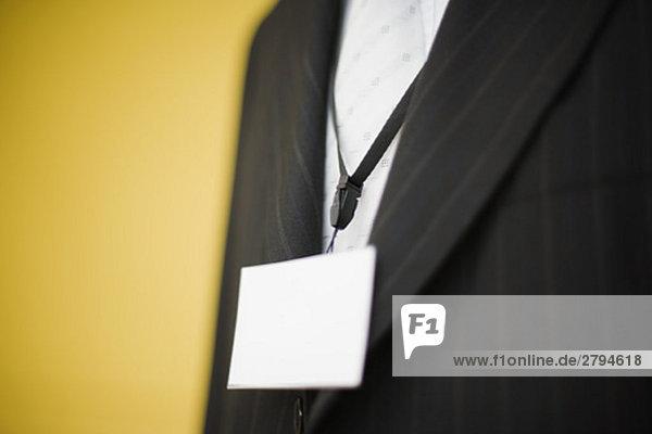 Mann im Anzug mit blankem Namensschild um den Hals  beschnitten
