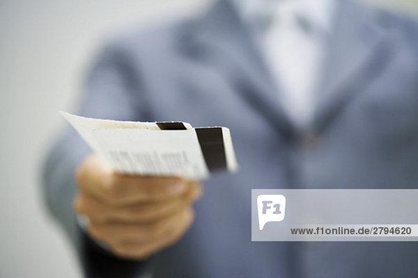Mann im Anzug  der Karten aushändigt