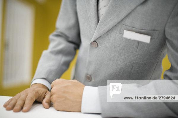 Mann im Anzug steht hinter der Theke und trägt ein leeres Namensschild.