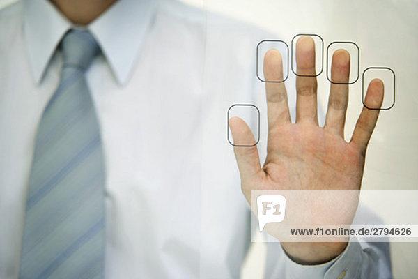 Mann drückt Fingerspitzen auf Fingerabdruckleser