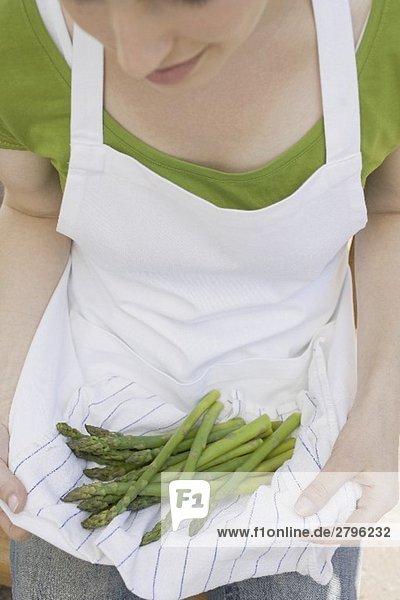 Junge Frau hält grünen Spargel in ihrer Schürze