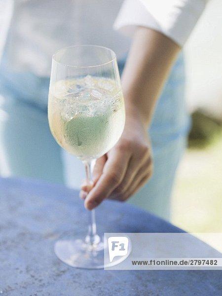 Frau greift nach Glas Weisswein mit Eiswürfeln auf Tisch Frau greift nach Glas Weisswein mit Eiswürfeln auf Tisch