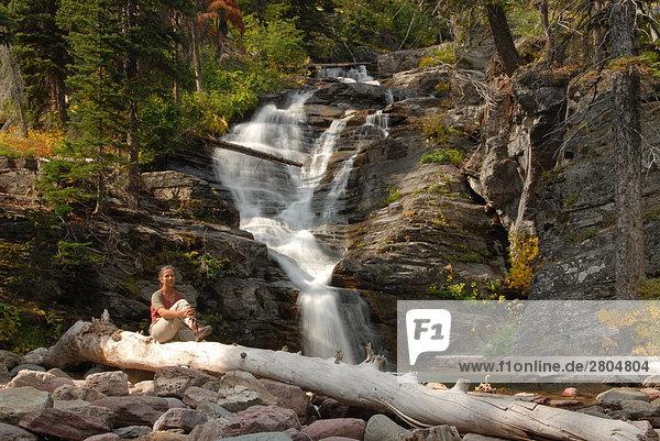 Frau sitzt auf Log in der Nähe von Wasserfall  Glacier National Park  Montana  USA