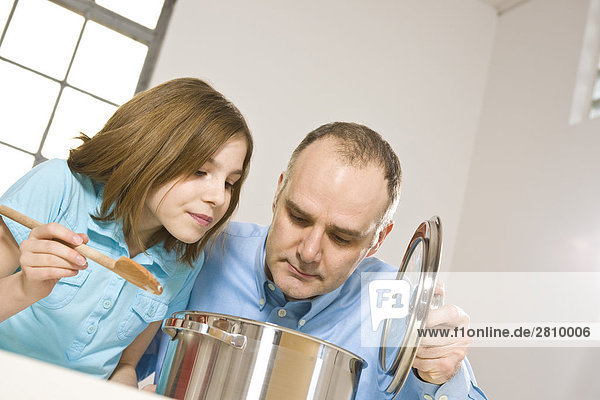 Man with his daughter smelling food in kitchen