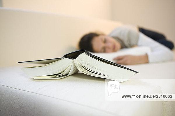 Nahaufnahme-Buch mit Mädchen auf der Couch liegen, Nahaufnahme-Buch mit Mädchen auf der Couch liegen