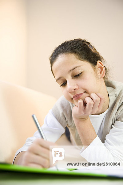 Mädchen auf Blatt Papier schreiben
