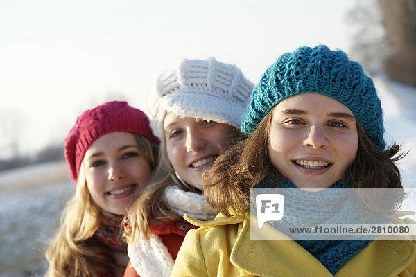 Teenage girls smiling in warm clothing