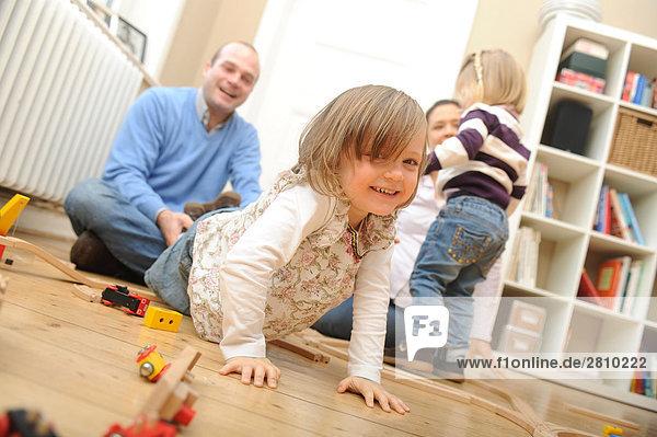 Mädchen mit Spielzeug und ihrem Vater zieht spielerisch ihr spielen