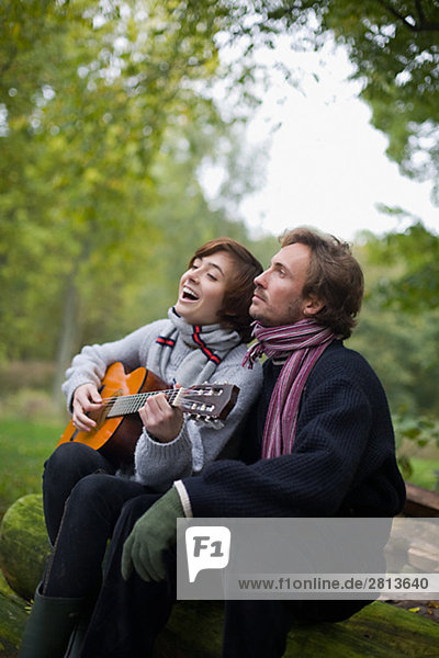 A young couple playing the guitar in the garden Sweden.