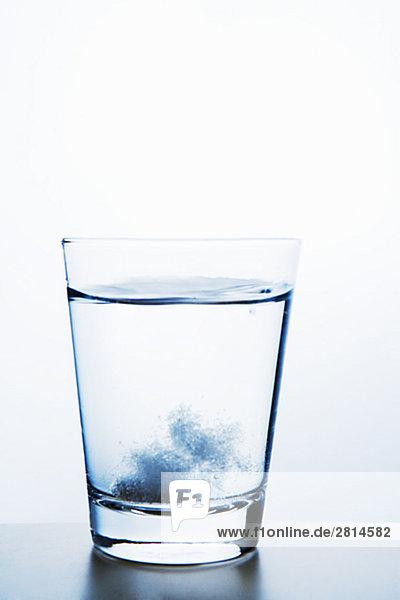 Eine Brausetablette und ein Glas Wasser Nahaufnahme.