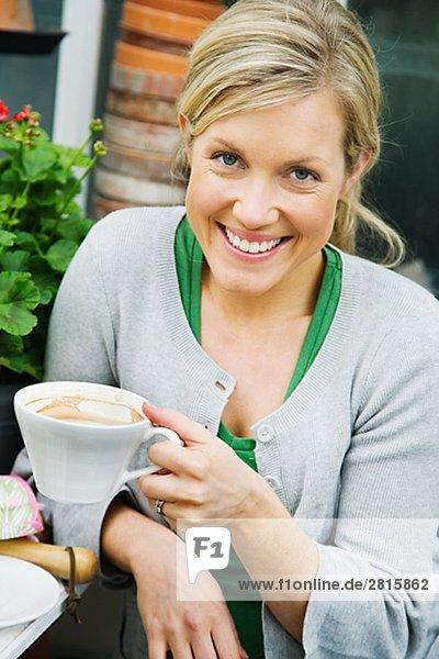 blond Frau trinken Kaffee Treibhaus