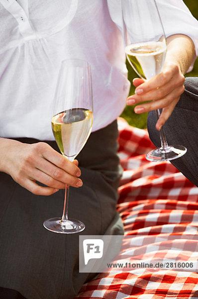 A woman holding two glasses of champagne Copenhagen Denmark.