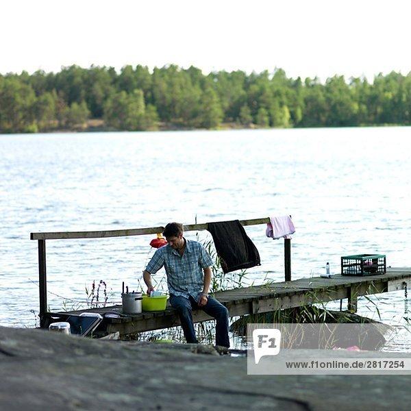 Ein Mann tun die Gerichte sitzen auf einer Mole Schweden.