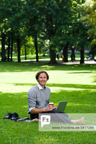 Ein Mann mit einem Laptop in einem Park Schweden.