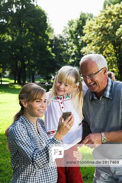 Frau älterer Mann and Girl Fotografieren im Park Schweden.