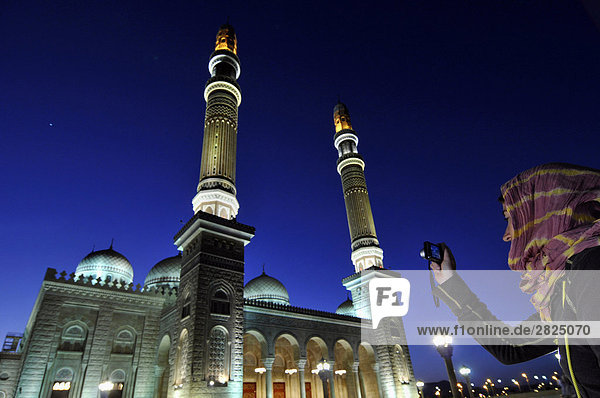 Yemen  Sanaa  the new mosque at dusk  tourist taking photograph