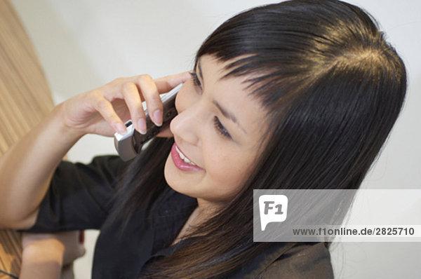 Vogelperspektive Portrait lächelnd asiatische Frau am Telefon