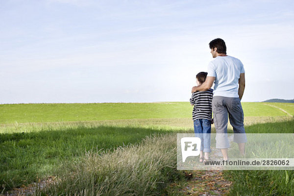 young father and his son looking the horizon in the countryside