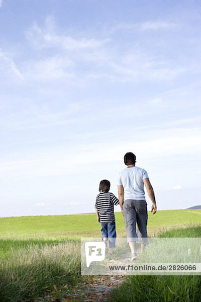 young father and his son walking on path in the countryside