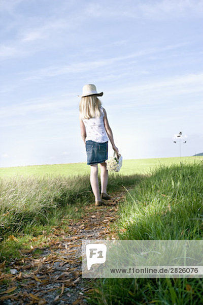 young girl with basket full of flowers walking on path in the countryside