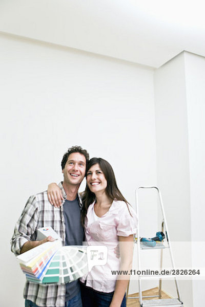 young couple choosing colour for wall in new apartment with colour chart