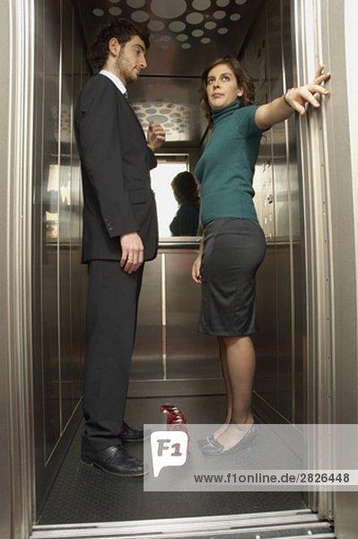 Kaufmann und Frau Kollegin im Aufzug zusammen Woman looking verärgert