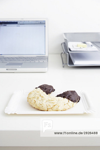 still life of pastry on paper plate on office desk