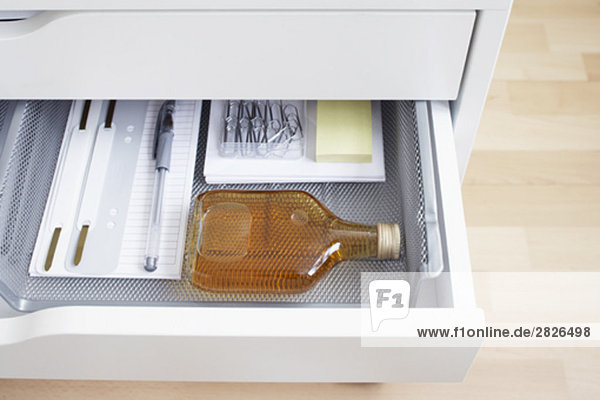 view into open desk drawer containing small alcohol bottle