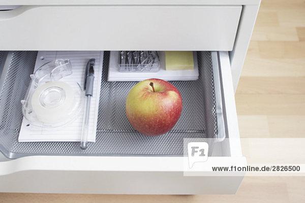 Blick in offenen Schreibtischschublade mit roten Apfel
