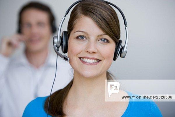 Porträt der jungen weiblichen Call Center Agent mit männlichen Kollegen im Hintergrund