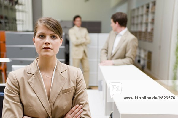 Porträt der jungen geschäftsfrau mit männlichen Kollegen im Hintergrund